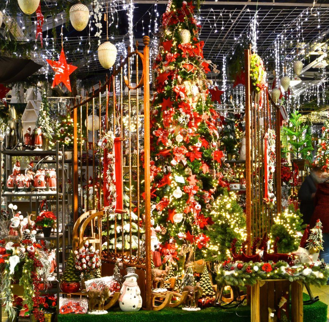 Eingangsbereich Weihnachtsbazar mit großem traditionell geschmücktem Weihnachtsbaum hinter einem großen Gusseisernen Tor.