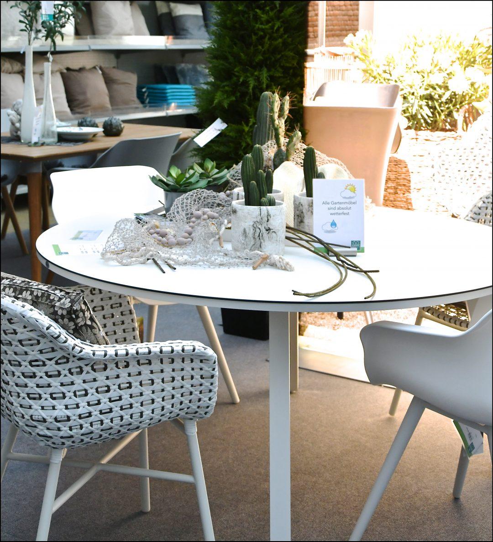 Ein runder weißer Tischmit weißen Stühlen daneben. Auf dem Tisch liegt eine Deko bestehend aus einem Fischernetz, Kakteen und Sukkulenten im Topf.