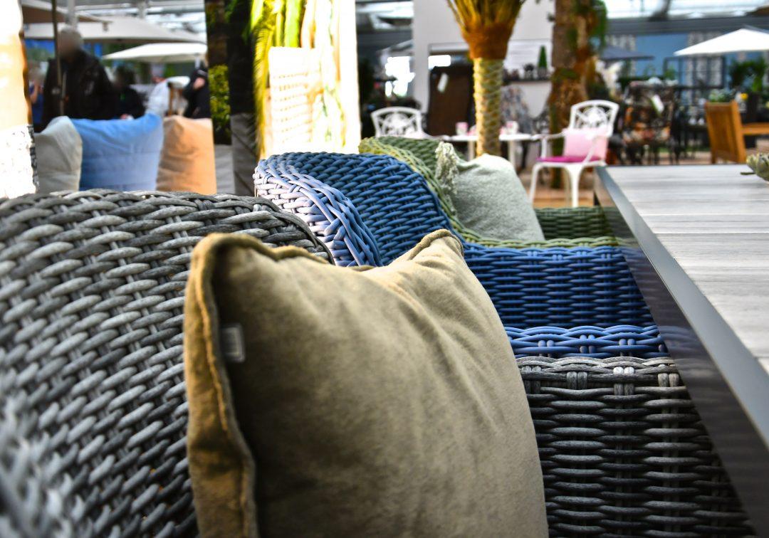 Drei Stühle in den Farben anthrazir, blau und grün. Auf dem vorderen und hintersten Stuhl liegt jeweils ein Kissen. Im Hintergrund sieht man unscharf weitere Gartenmöbel und Palmen
