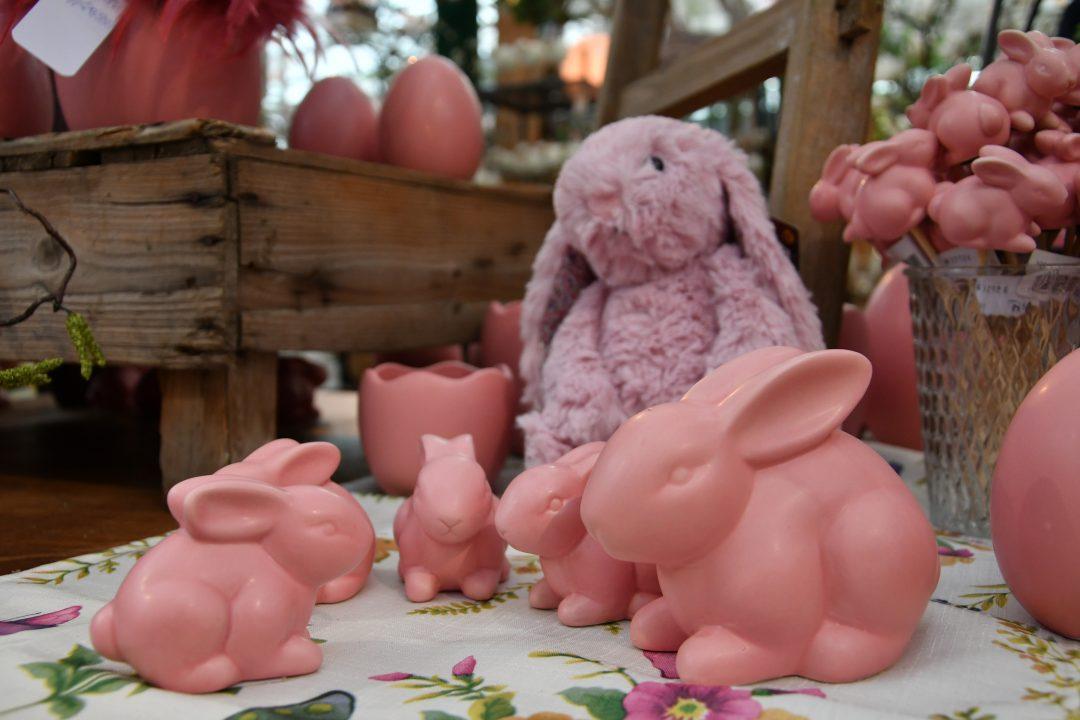 Auf diesem Bild erkennt man rosafarbene Keramik Osterhasen und einen flauschigen Osterhasen in der selben Farbe. Sie stehen auf einer blumigen Tischdecke und im Hintergrund erkennt man weitere österliche Dekoelemente.