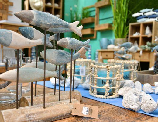 Maritime Dekoration, man sieht links Holzfische und rechts unscharf Steine, Kerzen in Fischernetz und weitere blau-türkis gehaltene Dekoelemente.