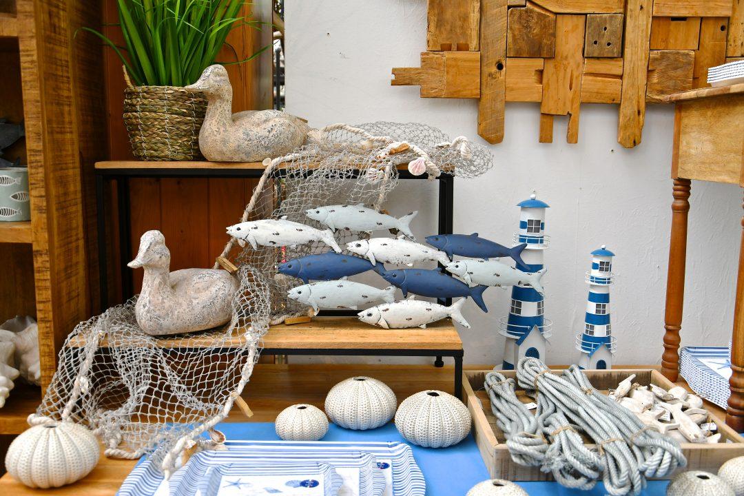 Maritime Dekoration. Man sieht Leuchttürme, ein Fischernetz mit Fischen und daneben Enten die Sommerfeeling widerspiegeln