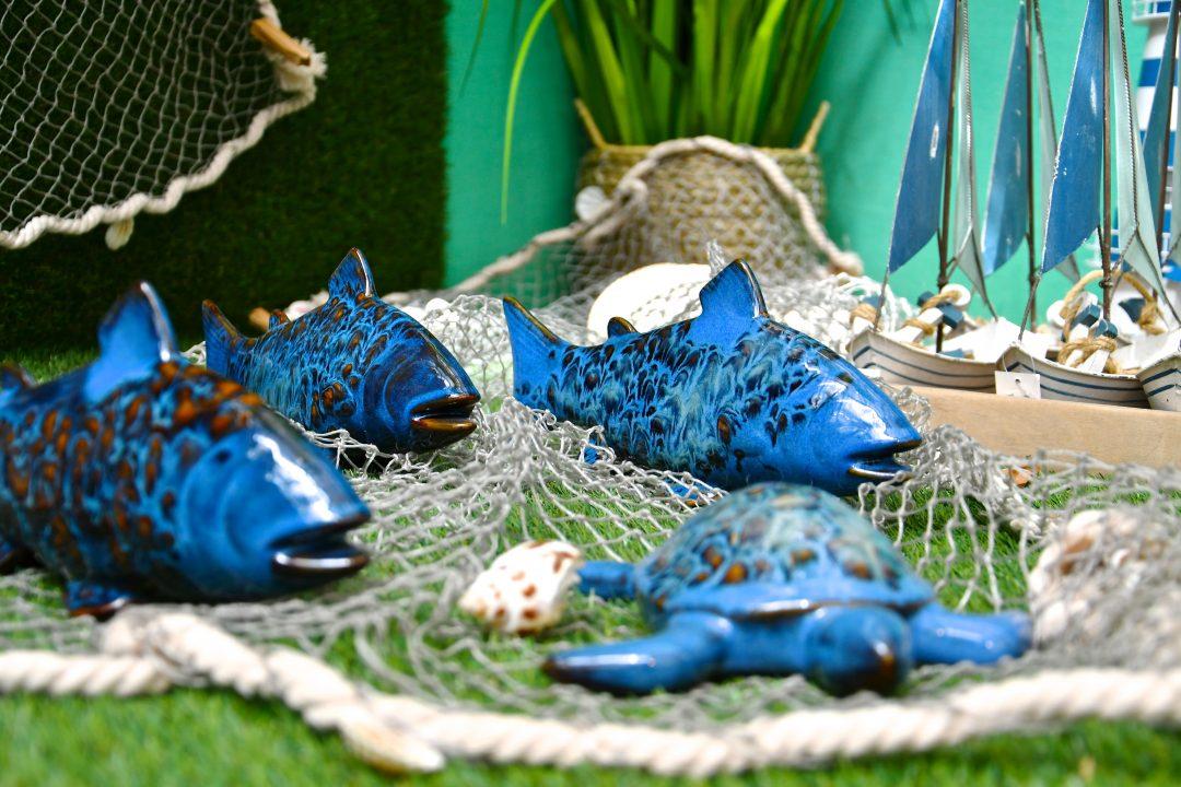 Maritime Dekoration. Blaue Porzellan Fische und eine Schildkröte auf einem Fischernetz. Rechts sieht man kleine blau weiße Segelboote.