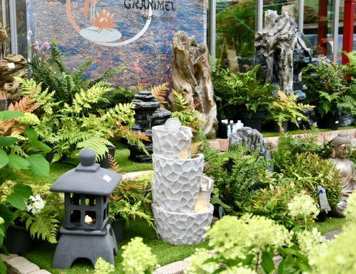 Outdoorbrunnenausstellung im Gartencenter. Drumherum stehen Pflanzen.