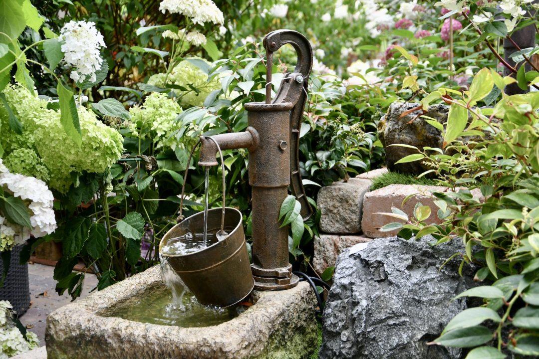 Outdoorbrunnen in Pumpenoptik. Dahinter stehen Rispenhortensien. Wasser fließt aus dem Hahn in einen Eimer.