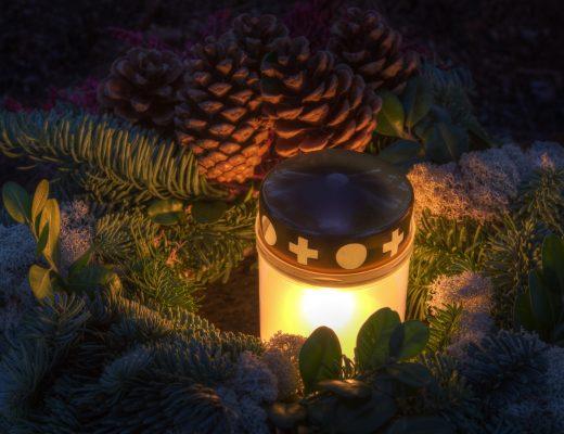 Kerze auf einem Grab umgeben von Tannenzweigen und Zapfen.
