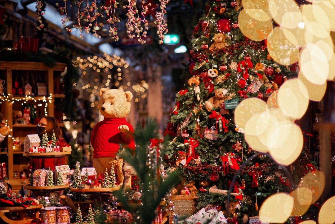 Künstlicher Teddybär mit rotem Pullover neben einem festlich geschmückten Weihnachtsbaum.